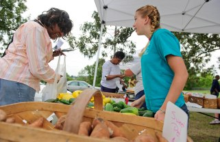 UNCG photo by Chris English - 09/20/2011 - UNCG communication studies student Hannah Harris, right, works with customers at the Warnersville Farmers Market on Tuesday September 20, 2011. The neighborhood has many low-income residents who don't have reliable transportation to get to a grocery store, so it is difficult for them to find fresh fruits and vegetables. The communications Studies department is working on easier access to healthy foods to areas called food deserts.