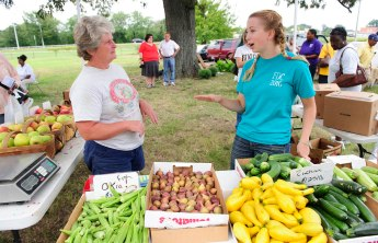UNCG photo by Chris English - 09/20/2011 - UNCG communication studies student Hannah Harris, right, talks with a vender at the Warnersville Farmers Market on Tuesday September 20, 2011.  The neighborhood has many low-income residents who don't have reliable transportation to get to a grocery store, so it is difficult for them to find fresh fruits and vegetables.  The communications Studies department is working on easier access to healthy foods to areas called food deserts.
